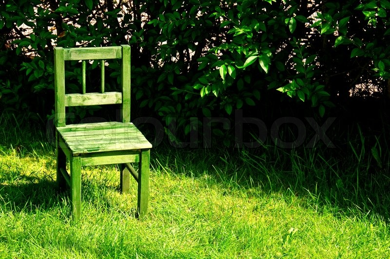 Find the perfect green chair stock photo. a small green chair in a garden stock