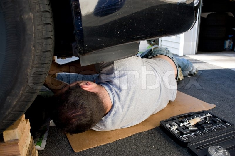 A young man laying underneath a car doing repairs or maintenance on the vehicle  Stock Photo