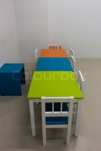 Inside of the kindergarten classroom with colorful desks ...