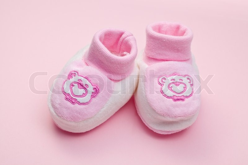 Pink baby shoes on color background