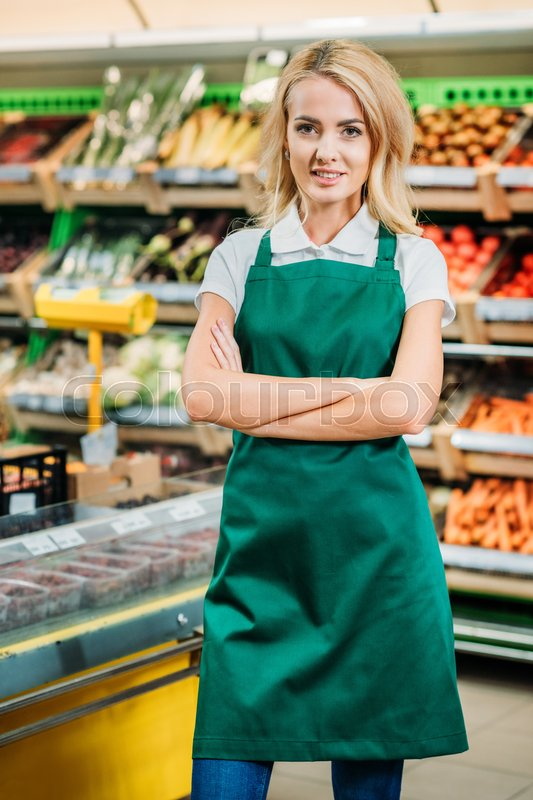Portrait of shop assistant in apron with arms crossed looking at camera in grocery shop  Stock