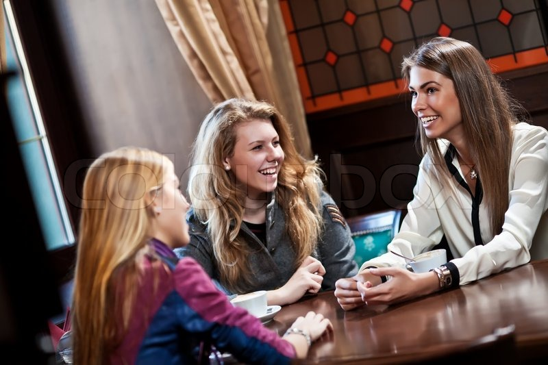 Pretty girlfriends talk and drink coffee in cafe house  Stock Photo  Colourbox