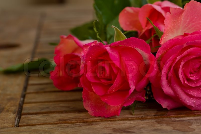 Bouquet Of Pink Roses In Water Droplets On Wooden Table