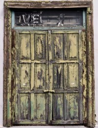 A very old wooden door, painted green, with weathered ...