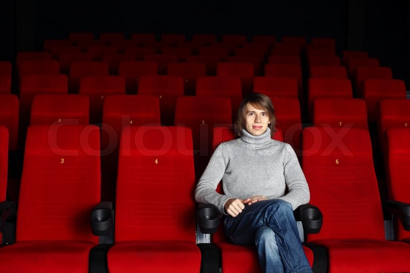 movie theatre chairs for home chair cover christmas decorations young man sitting in the cinema alone | stock photo colourbox