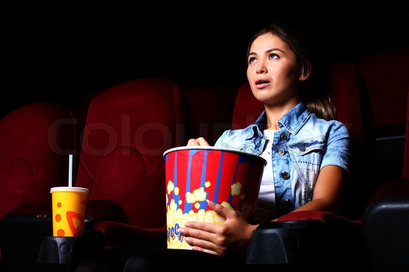 One young girl watching movie in cinema  Stock Photo