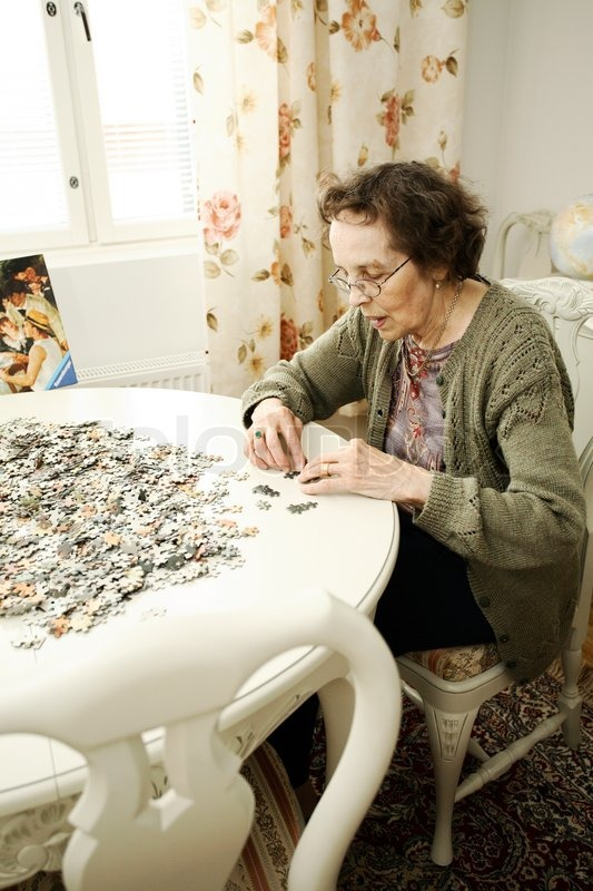Old lady concentrating on a huge jigsaw puzzle at her living room table  Stock Photo  Colourbox