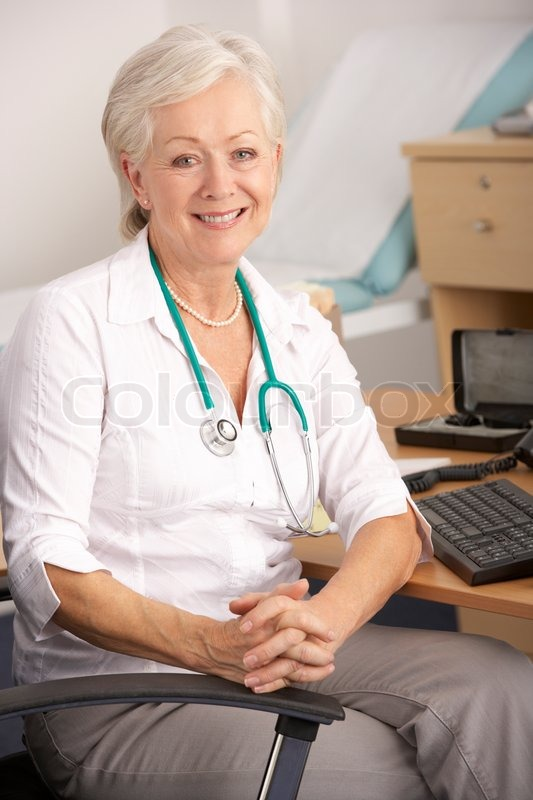 Britische weibliche Gp am Schreibtisch sitzend  Stockfoto