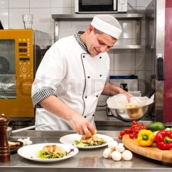 Kitchen Chief Island With Range Chef Preparing Food In The At Stock Photo Colourbox
