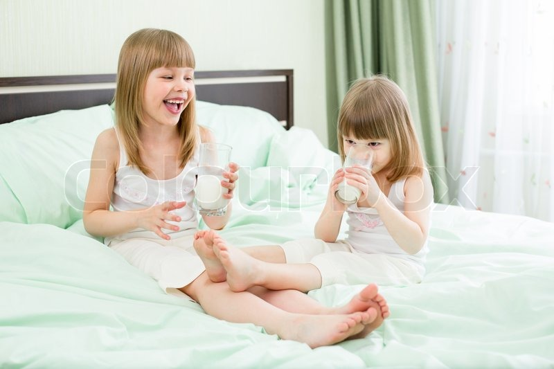 Cute Little Girls Laughing Wallpaper Two Little Girls Drinking Milk From Glasses On Bed Stock
