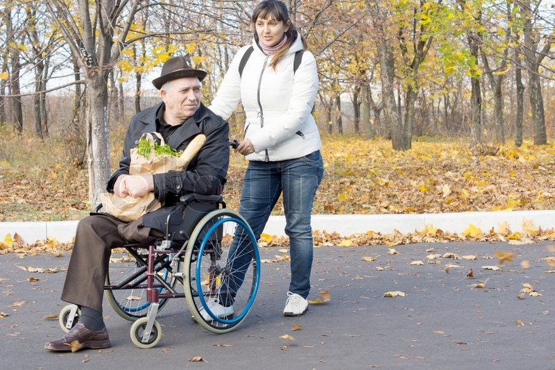 Woman helping a disabled pensioner in a wheelchair pushing