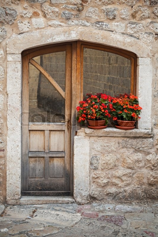 Old wooden door with red flowers on the windowsill  Stock Photo  Colourbox