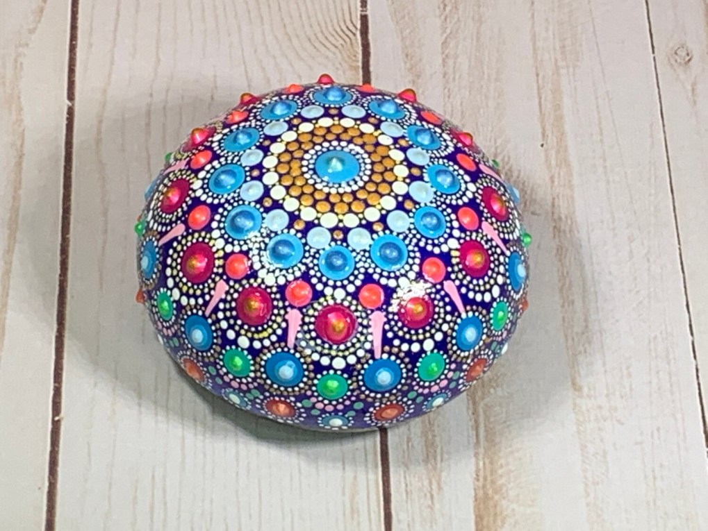 Mandala rock in shades of blue and red-pink
