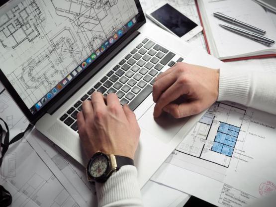 事務事業のワークスペーステーブルデスクでは、MacBookのラップトップコンピュータの青写真をガジェット床家の計画を立案AutoCADのコーレルノートジャーナルは、ストラップの男、男性の手の腕時計型の設計をペンレイアウトします