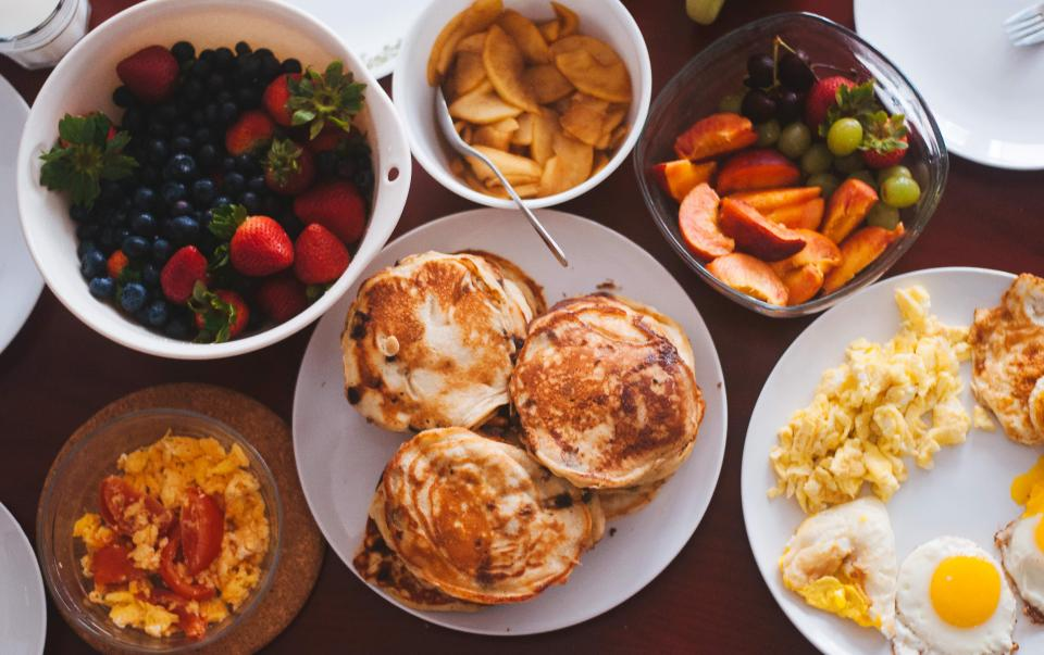 food eat breakfast eggs sunny side up scrambled yolk pancakes fruits grapes strawberries spread plates forks cups mugs glasses bowls flatlay still bokeh