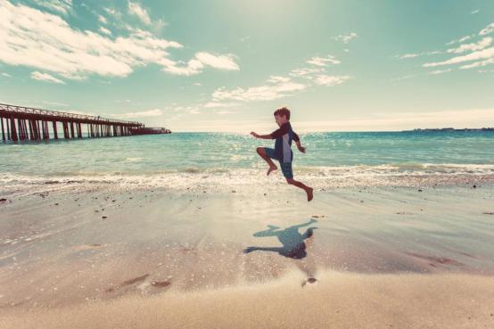 少年のビーチの砂の海岸水波海海の桟橋日差し晴れた夏空の雲の人々楽しいジャンピング子