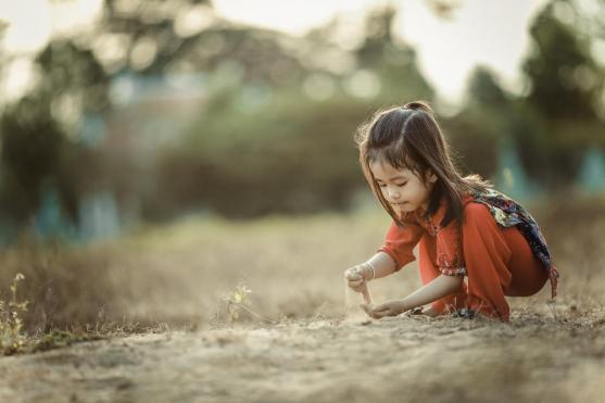 人の女の子の子供の子供一人の芝生の再生砂のボケ