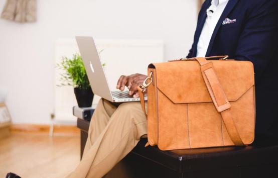 ワーキングラップトップ・コンピュータ技術ビジネスオフィスレザーバッグブリーフケーススーツケースの人のスーツの男の男タイピング