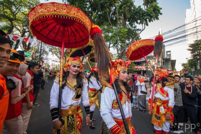Balinese men with dark black eye and beard makeup in clothes of red and white with gold accents