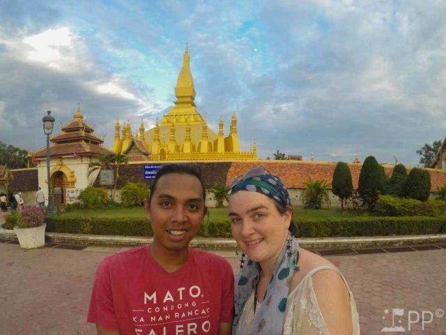 Puzzled Pilgrim team in front of large golden temple in Laos