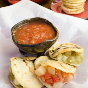 Corn gorditas stuffed with potatoes in tomato and tomatillo salsas. A vegan recipe.