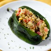 This vegan chickpea tuna salad of mashed chickpeas, tomato, onion, serrano pepper, mayo, olives, and capers is stuffed into a poblano pepper.