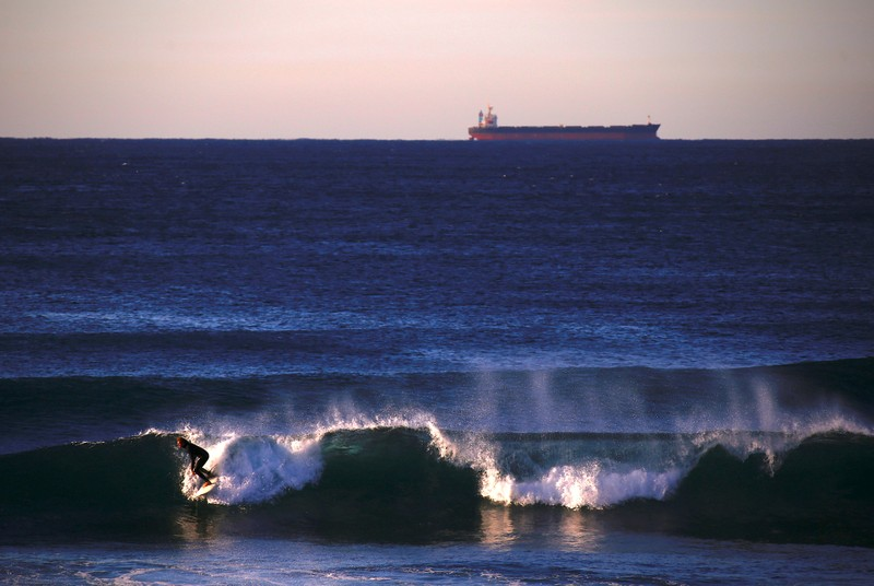 FILE PHOTO: A ship waiting to be filled with a load of coal can be seen behind a surfer riding a wave at Merewether Beach in Newcastle, located north of Sydney