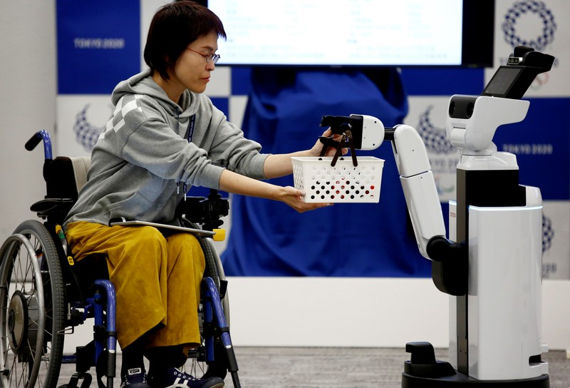 Toyota's Human Support Robot delivers a basket to a woman in a wheelchair at a demonstration of Tokyo 2020 Robot Project for Tokyo 2020 Olympic Games in Tokyo