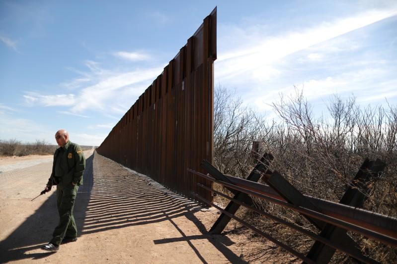 Supervisory Border Patrol Agent Joe Romero walks next to new bollard-style U.S.-Mexico border fencing in Santa Teresa