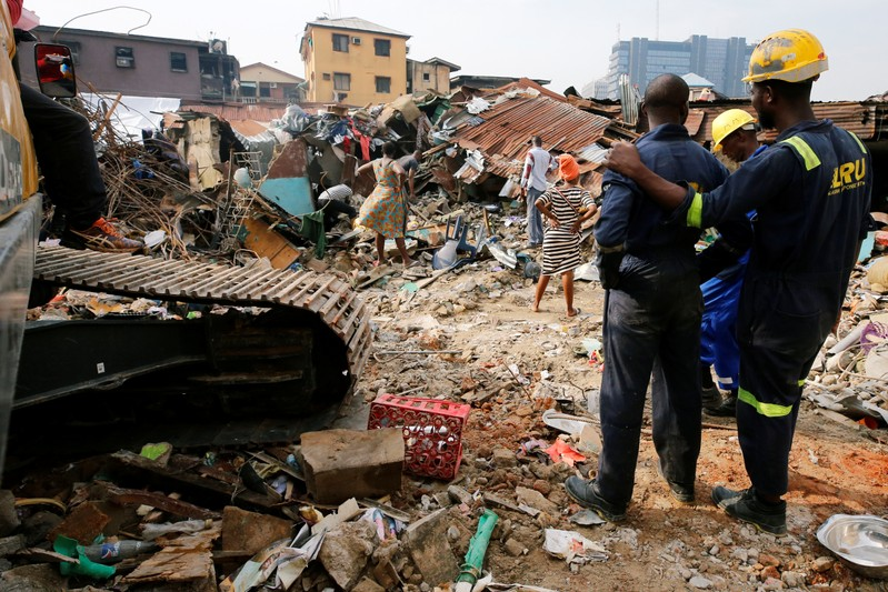 Rescuers are seen as people search for belongings at the site of a collapsed building in Nigeria's commercial capital of Lagos