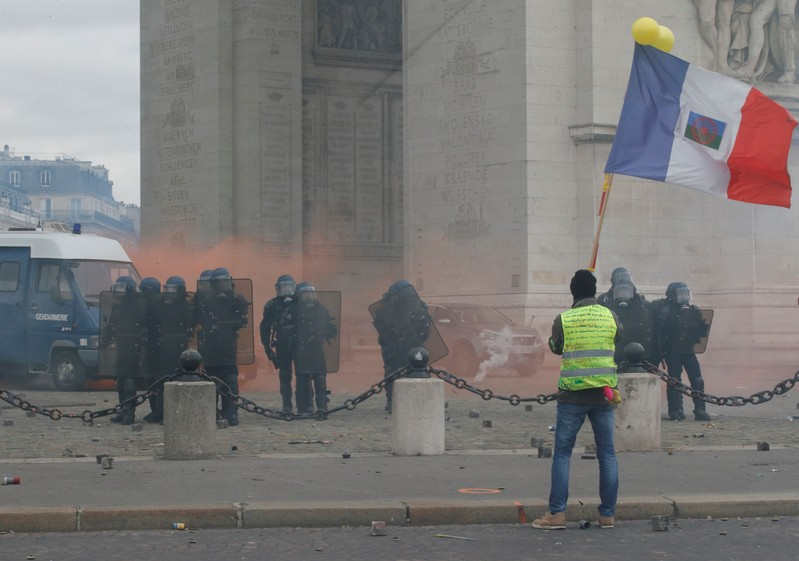 Protester wearing a yellow vest holds a flag during a demonstration by the