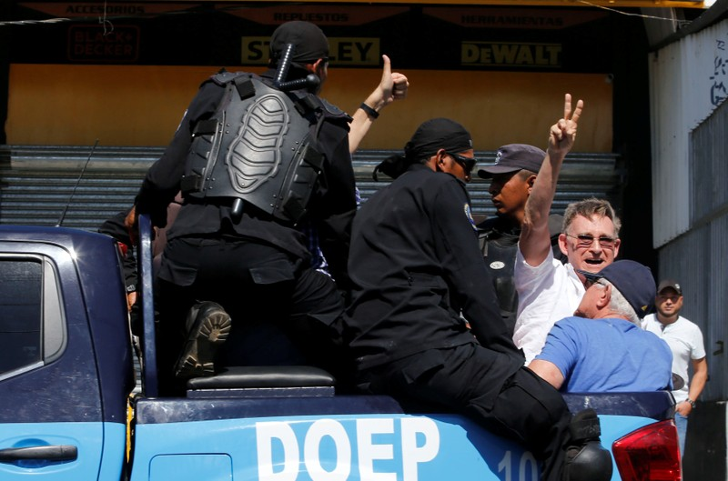 A demonstrator gestures as he is detained by riot police during a protest against the government of Nicaragua's President Daniel Ortega in Managua