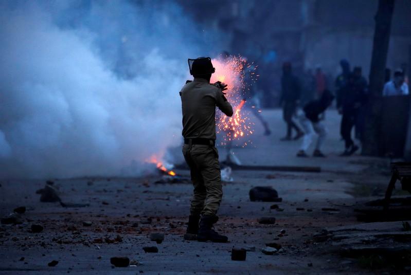 FILE PHOTO: Indian police officer fires tear gas shell towards demonstrators in Srinagar
