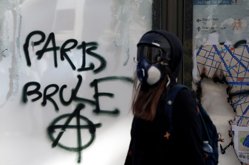 Protester walks past a graffiti during a demonstration by the