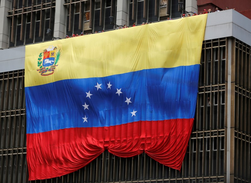 FILE PHOTO: A Venezuelan flag hangs from a building near the national election board as acting President Maduro registered as a candidate for president in the April 14 election in Caracas