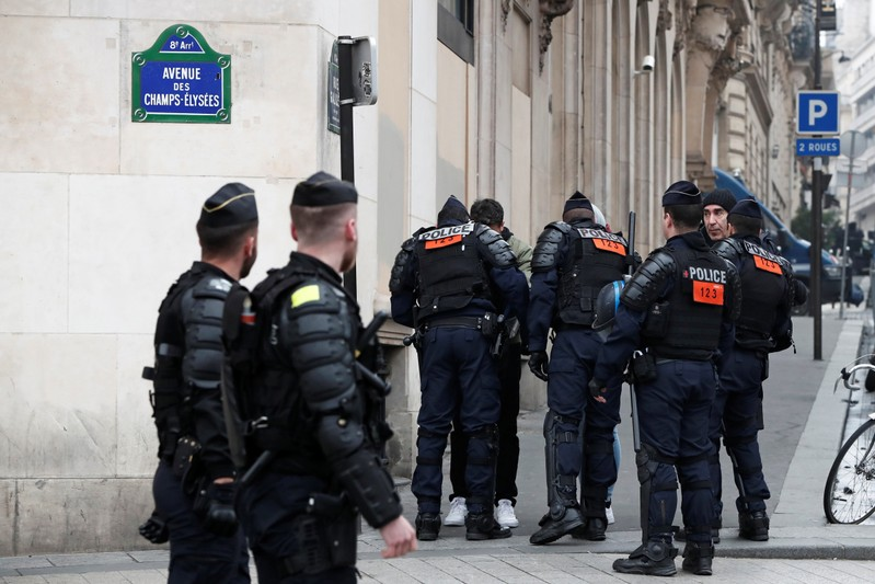 French riot police officers check people on the Champs-Elysees avenue during the Act XIX (the 19th consecutive national protest on a Saturday) of the
