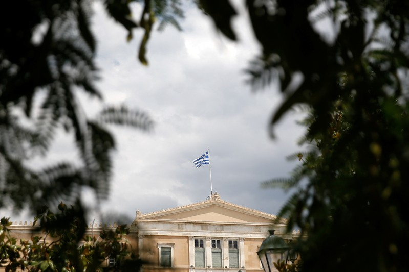 FILE PHOTO: A Greek flag flutters atop the parliament building in Athens