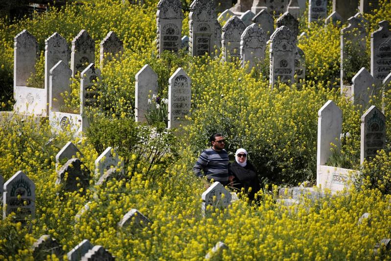 People visit a cemetery in al-Shaar neighborhood of Aleppo