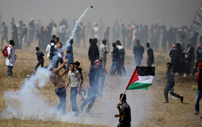 Palestinian demonstrator hurls back a tear gas canister fired by Israeli forces during protest marking the 71st anniversary of 'Nakba' at the Israel-Gaza border fence in the southern Gaza Strip