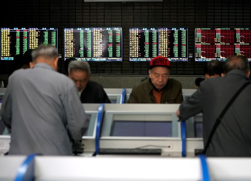 Investors look at computer screens showing stock information at a brokerage house in Shanghai