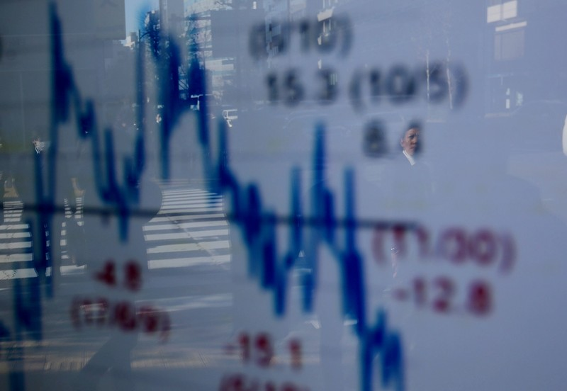 A man is reflected on an electronic board showing a graph analyzing recent change of Nikkei stock index outside a brokerage in Tokyo
