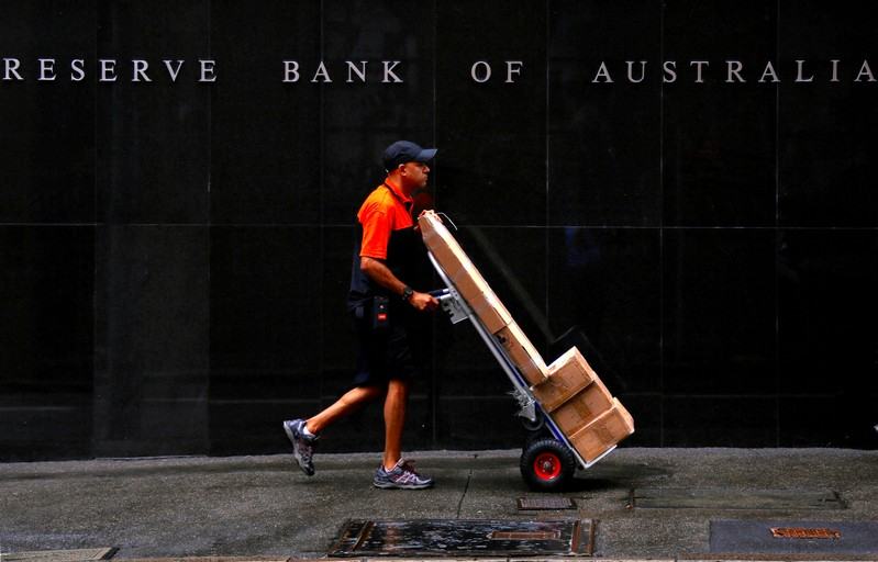 FILE PHOTO: A worker delivering parcels pushes a trolley past the Reserve Bank of Australia building in central Sydney, Australia