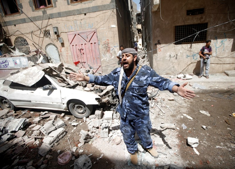A Houthi security officer reacts at the site of an air strike launched by the Saudi-led coalition in Sanaa