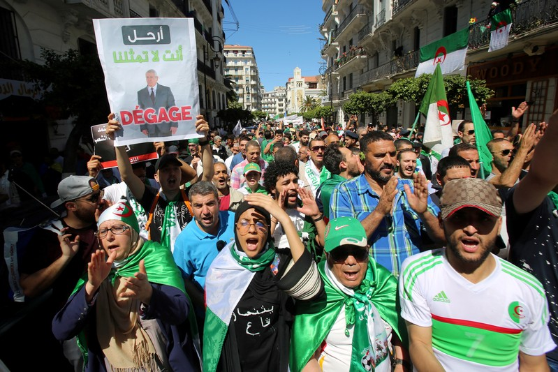 FILE PHOTO: A demonstrator holds a banner depicting interim president Abdelkader Bensalah during a protest demanding the removal of Algeria's ruling elite in Algiers