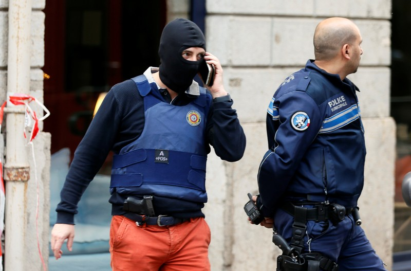 Police officers are seen near the site of a suspected bomb attack in central Lyon