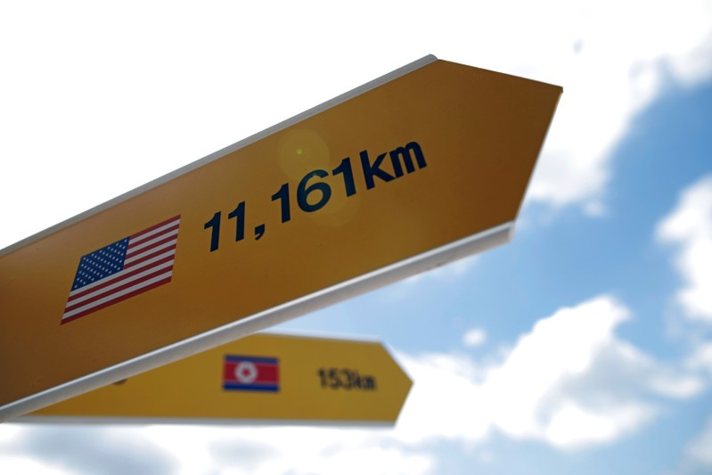 Directional signs bearing North Korean and U.S. flags are seen near the demilitarized zone in Paju