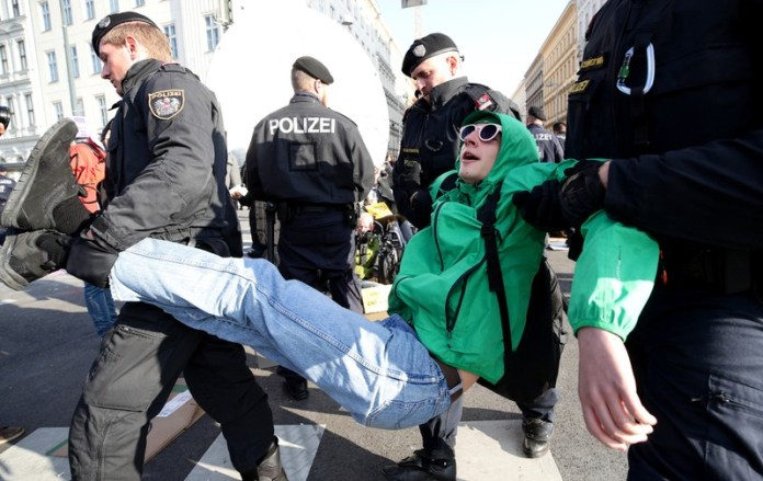 Police officers pull out a climate change activist as activists block a road during the Extinction Rebellion protest in Vienna