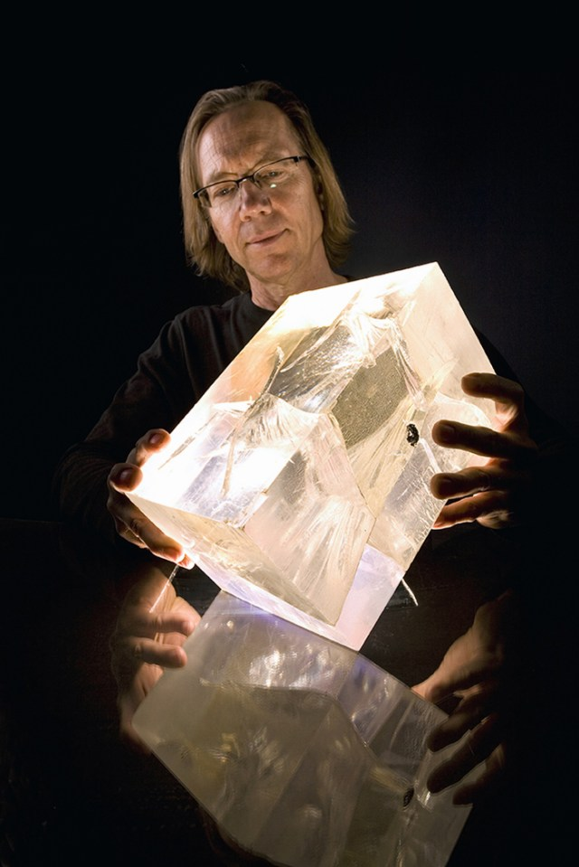 Portrait of Paul Johnson against a black background, holding an illuminated block of plastic.