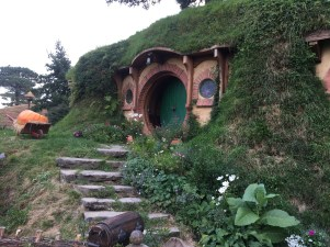 image of a small circular door, a hobbit hole from the lord of the rings book. There are lots of plants surrounding the house.