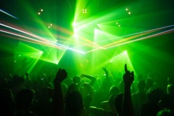 clubbing scene with ggreen lights and strobe lighting. People are raising their hands and dancing